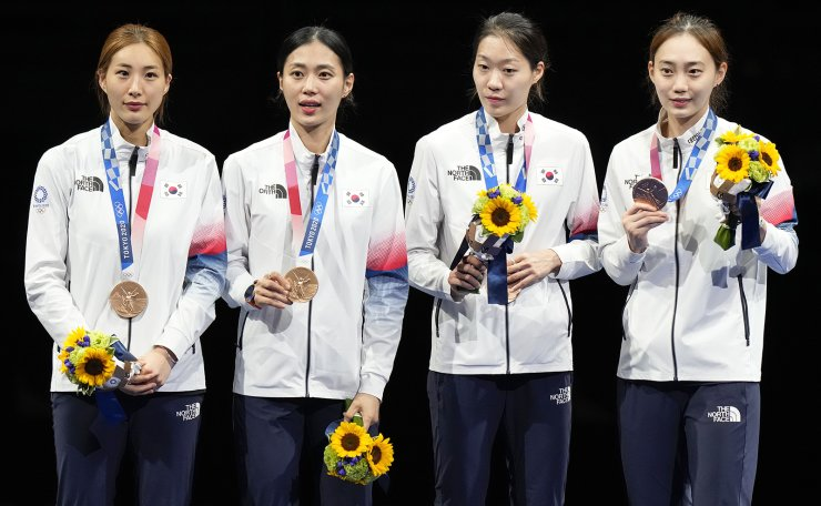 Bronze medalists of South Korea celebrate on the podium of the women's Sabre team at the 2020 Summer Olympics, Saturday, July 31, 2021, in Chiba, Japan. AP