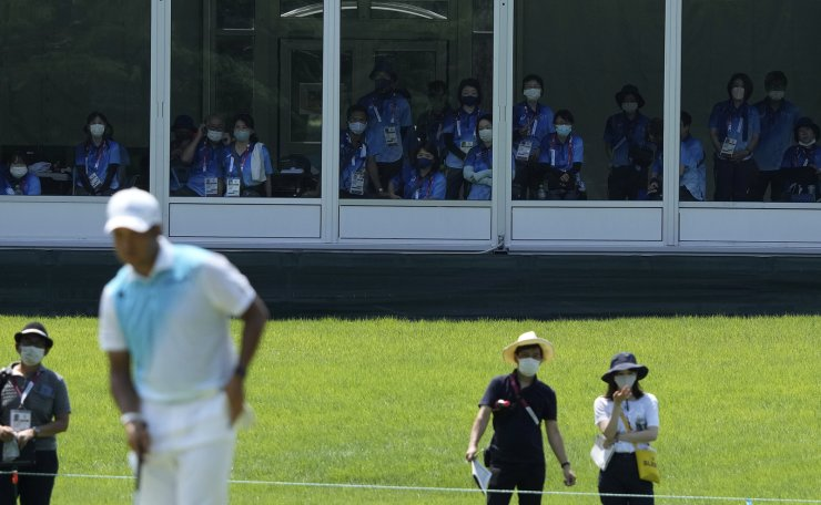 Volunteers watch Hideki Matsuyama of Japan arriving to 7th green during the final round of the men's golf event at the 2020 Summer Olympics on Sunday, Aug. 1, 2021, in Kawagoe, Japan. AP