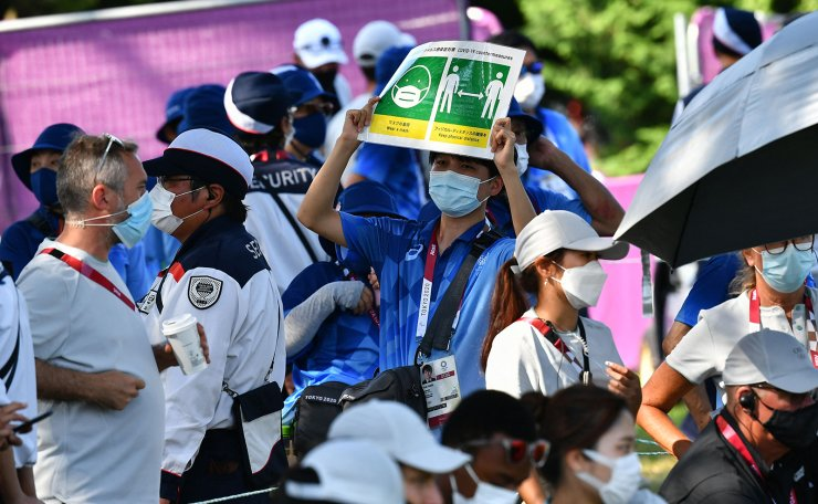 A volunteer holds up a sign to remind people to adhere to Covid-19 protocols during round 4 of the men?s golf individual stroke play during the Tokyo 2020 Olympic Games at the Kasumigaseki Country Club in Kawagoe on August 1, 2021. AFP