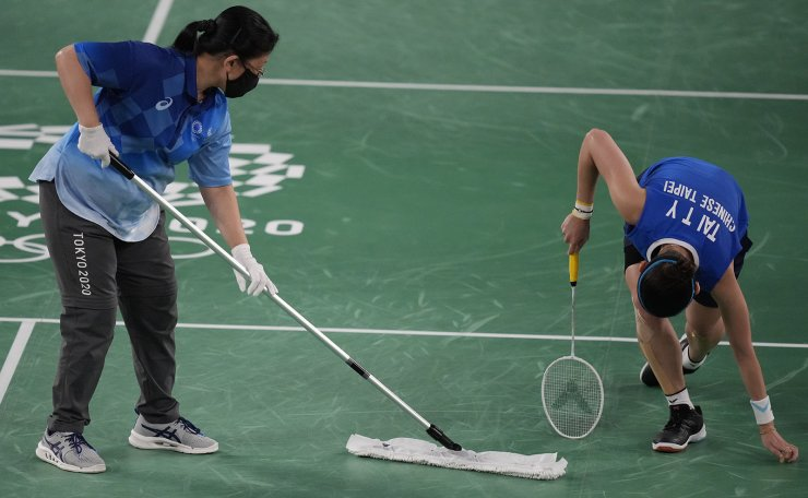 A ground staff member cleans the court as Taiwan's Tai Tzu-Ying gets up during a match against China's Chen Yu Fei in women's singles badminton gold medal match at the 2020 Summer Olympics, Sunday, Aug. 1, 2021, in Tokyo, Japan. AP
