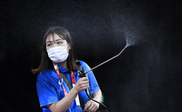 Tokyo 2020 Olympics - Wrestling - Greco-Roman - Men's 60kg - Repechage Round - Makuhari Messe Hall A, Chiba, Japan - August 2, 2021. Staff member disinfects the area around the wrestling mat. REUTERS
