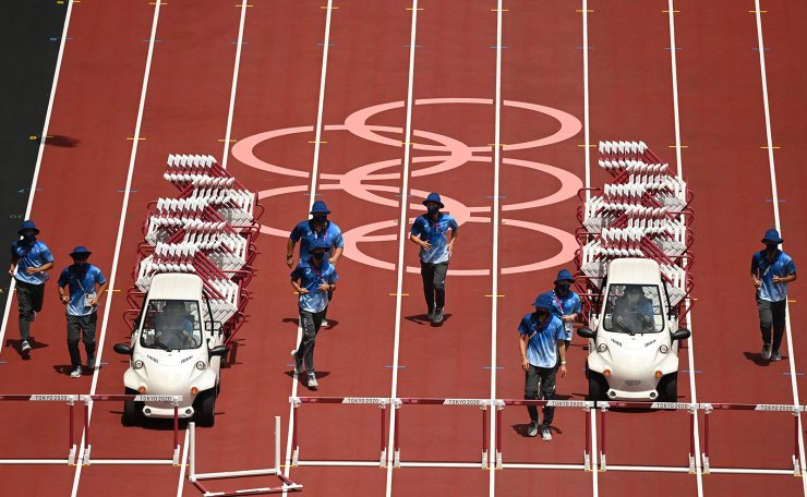 Staff remove hurdles from the track after the women's 100m hurdles final during the Tokyo 2020 Olympic Games at the Olympic Stadium in Tokyo on August 2, 2021. AFP