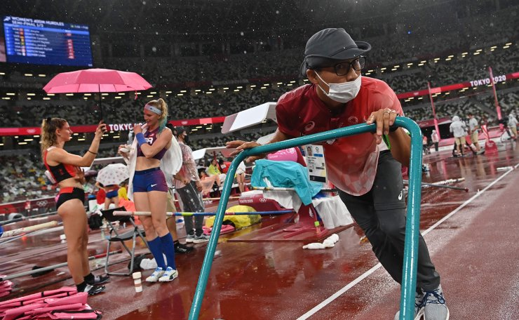 A staff member wipes the track as athletes shelter from the rain during the women's pole vault qualification during the Tokyo 2020 Olympic Games at the Olympic Stadium in Tokyo on August 2, 2021. AFP