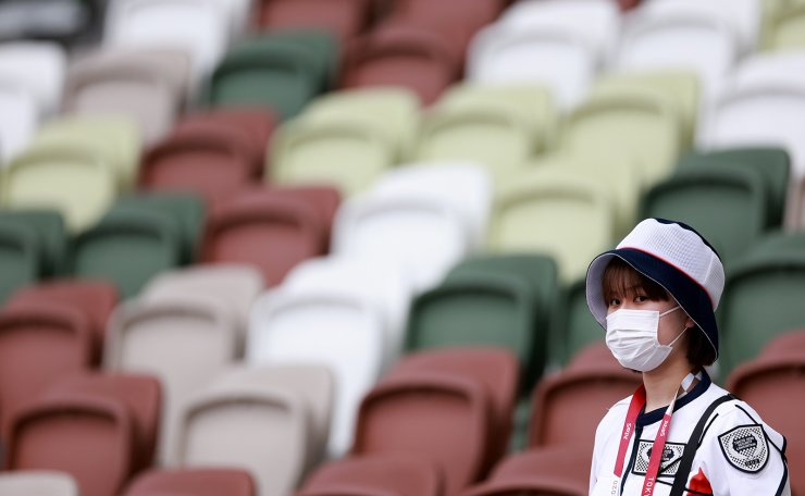 Tokyo 2020 Olympics - Athletics - Women's Javelin Throw - Qualification - Olympic Stadium, Tokyo, Japan - August 3, 2021. A member of staff wearing a mask before with empty seats seen in the background. REUTERS