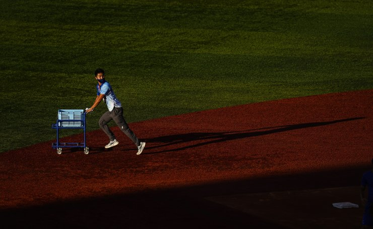 A volunteer runs out baseballs for Israel's warm up ahead of a baseball game against the Dominican Republic at the 2020 Summer Olympics, Tuesday, Aug. 3, 2021, in Yokohama, Japan. AP