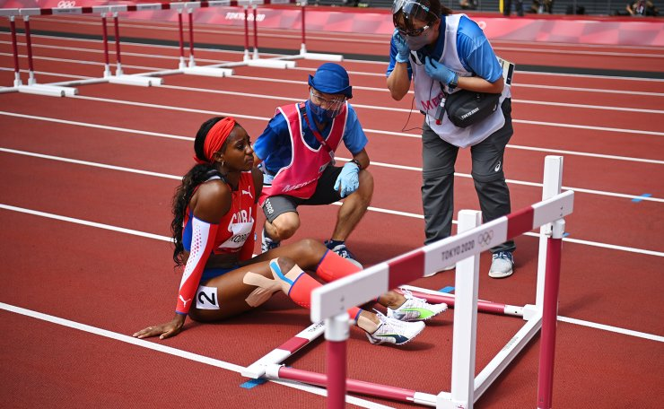 Tokyo 2020 Olympics - Athletics - Women's 100m Hurdles - Heptathlon 100m Hurdles - Olympic Stadium, Tokyo, Japan - August 4, 2021. Yorgelis Rodriguez of Cuba receives attention from medical staff wearing protective face masks after sustaining an injury during Heat 1. REUTERS