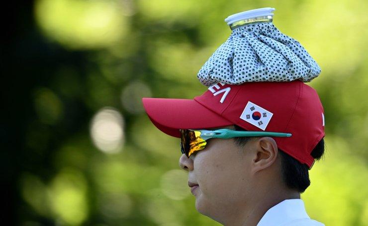 Tokyo 2020 Olympics - Golf - Women's Individual - Final - Round 2 - Kasumigaseki Country Club - Kawagoe, Saitama, Japan - August 5, 2021.  Kim Hyojoo of South Korea looks on as she holds an ice pack on her head to cool herself. REUTERS