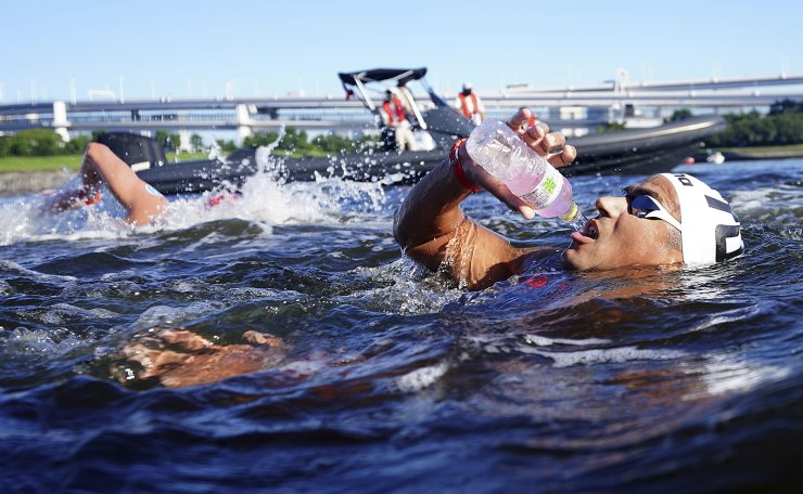 Oussama Mellouli, of Tunisia, grabs a drink while passing through the feeding station during the men's marathon swimming event at the 2020 Summer Olympics, Thursday, Aug. 5, 2021, in Tokyo. AP