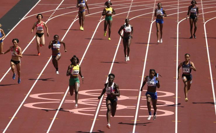 Daryll Neita, of Britain, center, anchors the team to a win in a semifinal of the women's 4 x 100-meter relay at the 2020 Summer Olympics, Thursday, Aug. 5, 2021, in Tokyo, Japan. AP