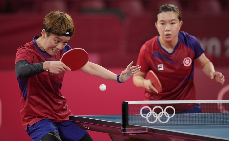 Hong Kong's Doo Hoi-kem, left, and Lee Ho-ching compete during the table tennis women's team bronze medal match against Germany's Petrissa Solja, left, and Shan Xiaona at the 2020 Summer Olympics, Thursday, Aug. 5, 2021, in Tokyo. AP