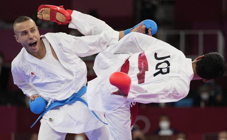 Abdel Rahman Almasatfa of Jordan, right, and Kalvis Kalnins of Latvia compete in the men's kumite -67kg elimination round for Karate at the 2020 Summer Olympics, Thursday, Aug. 5, 2021, in Tokyo, Japan. AP