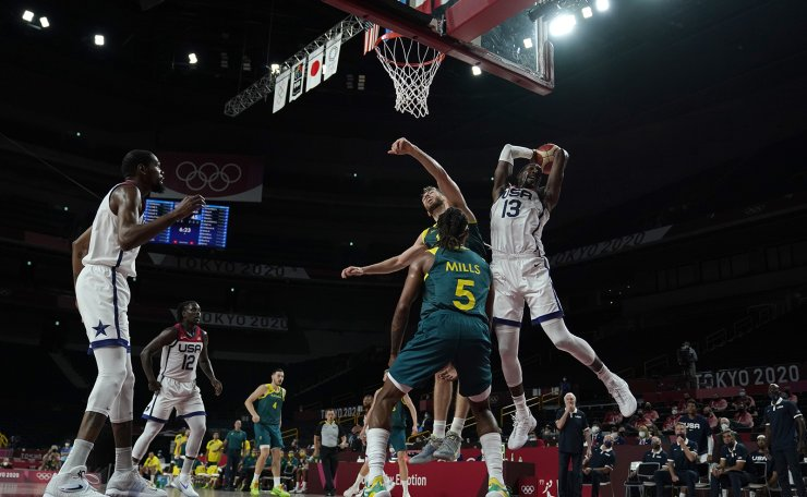 United States's Bam Adebayo (13) grabs a rebound over Australia's Patty Mills (5) and Nic Kay (15) during men's basketball semifinal game at the 2020 Summer Olympics, Thursday, Aug. 5, 2021, in Saitama, Japan. AP