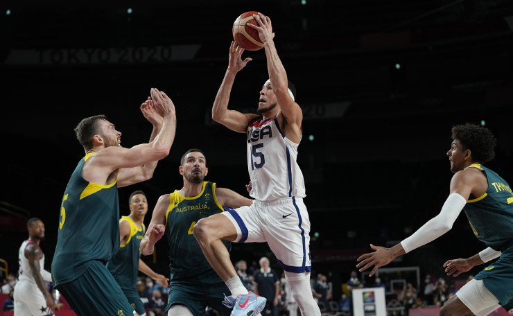 United States's Devin Booker (15) drives to the basket over Australia's Nic Kay (15) and Chris Goulding (4) during men's basketball semifinal game at the 2020 Summer Olympics, Thursday, Aug. 5, 2021, in Saitama, Japan. AP