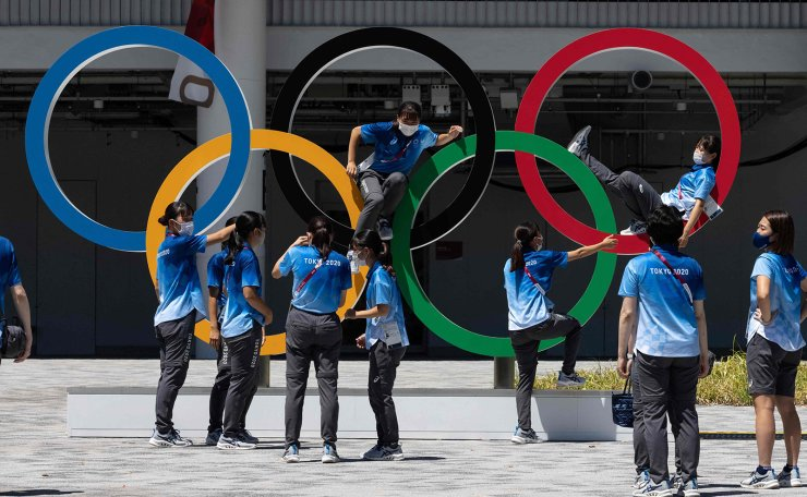 Staff members pose for pictures with the Olympic Rings outside the Olympic Stadium, main venue of the Tokyo 2020 Olympic Games, in Tokyo on August 5, 2021. AFP