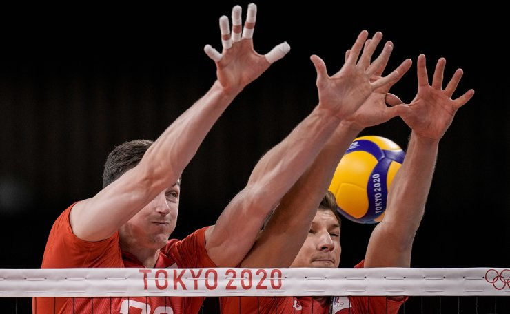 Yaroslav Podlesnykh, of the Russian Olympic Committee, left, blocks a ball during the men's volleyball semifinal match between Brazil and Russian Olympic Committee at the 2020 Summer Olympics, Thursday, Aug. 5, 2021, in Tokyo, Japan. AP