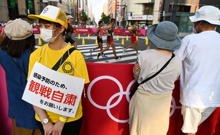 A volunteer wearing a sign reading 'Don't stop to watch the race due to the coronavirus disease restrictions' stands by people gathered to watch the men's 20km race walk final during the Tokyo 2020 Olympic Games at the Sapporo Odori Park in Sapporo on August 5, 2021. AFP