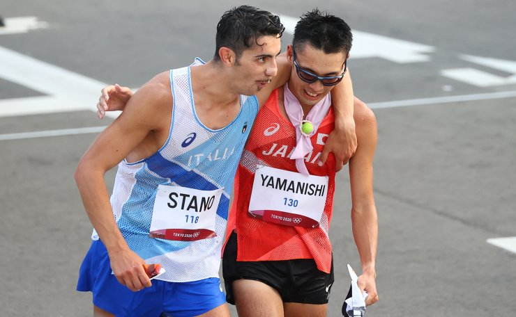 Tokyo 2020 Olympics - Athletics - Men's 20km Walk - Sapporo Odori Park, Sapporo, Japan - August 5, 2021. Gold Medallist Massimo Stano of Italy in action and Bronze Medallist Toshikazu Yamanishi of Japan embrace after competing. REUTERS