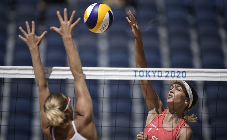 Anouk Verge-Depre, right, of Switzerland, takes a shot as Tina Graudina, of Latvia, defends during a women's beach volleyball Bronze match at the 2020 Summer Olympics, Friday, Aug. 6, 2021, in Tokyo, Japan. AP