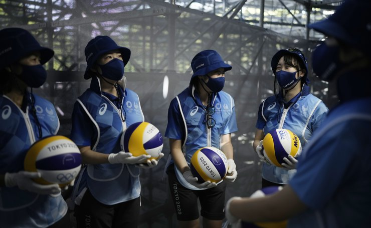 Olympic workers carry volley balls prior to the start of a women's beach volleyball Bronze match between Latvia and Switzerland at the 2020 Summer Olympics, Friday, Aug. 6, 2021, in Tokyo, Japan. AP