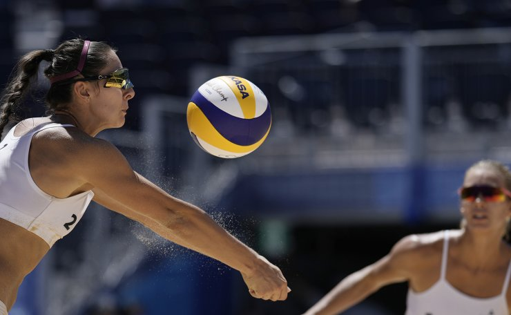 Anastasija Kravcenoka, left, of Latvia, returns a shot as teammate Tina Graudina watches during a women's beach volleyball Bronze match against Switzerland at the 2020 Summer Olympics, Friday, Aug. 6, 2021, in Tokyo, Japan. AP