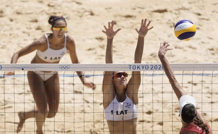Joana Heidrich, right, of Switzerland, takes a shot as Tina Graudina, middle, of Latvia,and teammate Anastasija Kravcenoka defend during a women's beach volleyball Bronze Medal match at the 2020 Summer Olympics, Friday, Aug. 6, 2021, in Tokyo, Japan. AP