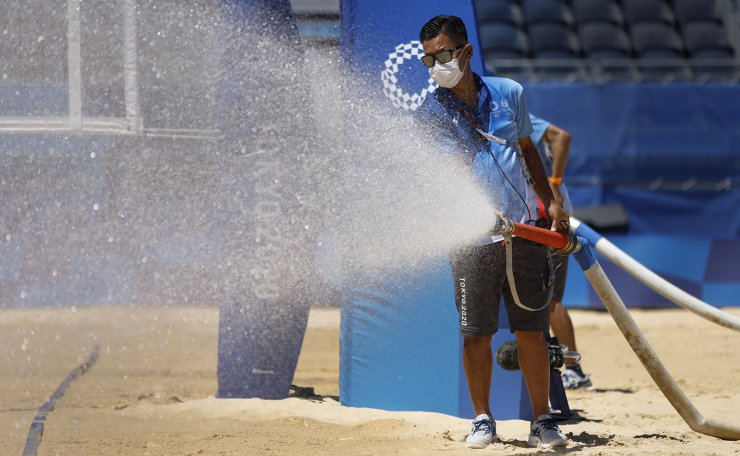 Tokyo 2020 Olympics - Beach Volleyball - Women - Gold medal match - Australia (Artacho del Solar/Clancy) v United States (April/Alix) - Shiokaze Park, Tokyo, Japan - August 6, 2021. A staff member prepares the playing surface before the gold medal match. REUTERS