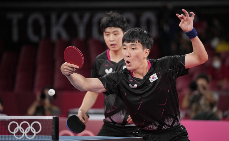 South Korea's Jeoung Young-sik, left, and Lee Sang-su compete during the table tennis men's team bronze medal match against Japan's Jun Mizutani and Koki Niwa at the 2020 Summer Olympics, Friday, Aug. 6, 2021, in Tokyo. AP