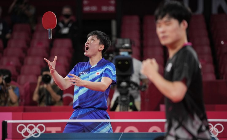 Japan's Tomokazu Harimoto throws paddle as he celebrates after winning a match during the table tennis men's team bronze medal matches against South Korea's Jang Woo-jin at the 2020 Summer Olympics, Friday, Aug. 6, 2021, in Tokyo. AP