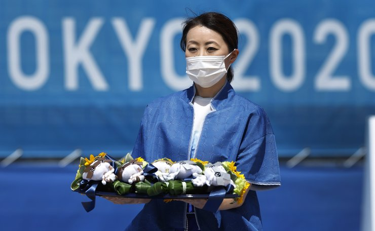 Tokyo 2020 Olympics - Beach Volleyball - Women - Medal Ceremony - Shiokaze Park, Tokyo, Japan - August 6, 2021. A staff member carries the medals during the ceremony. REUTERS