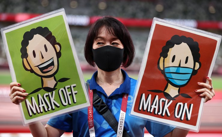 A staff member holds placards 'Mask Off' and 'Mask On' before the medal ceremonies during the Athletics events of the Tokyo 2020 Olympic Games at the Olympic Stadium in Tokyo, Japan, 06 August 2021. EPA