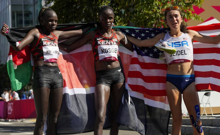 Gold medalist Peres Jepchirchir, left, of Kenya, stands with silver medalist and compatriot Brigid Kosgei, centre, and bronze medalist Molly Seidel, right, of the United States, following the women's marathon at the 2020 Summer Olympics, Saturday, Aug. 7, 2021, in Sapporo, Japan. AP