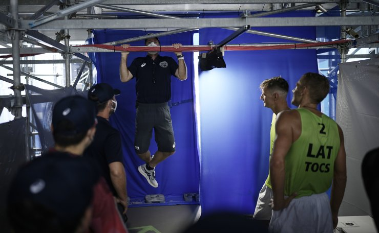 A referee does a chin up as Martins Plavins, second from right, of Latvia, and teammate Edgars Tocs, watch prior to the start of a men's beach volleyball Bronze Medal match against at the 2020 Summer Olympics, Saturday, Aug. 7, 2021, in Tokyo, Japan. AP