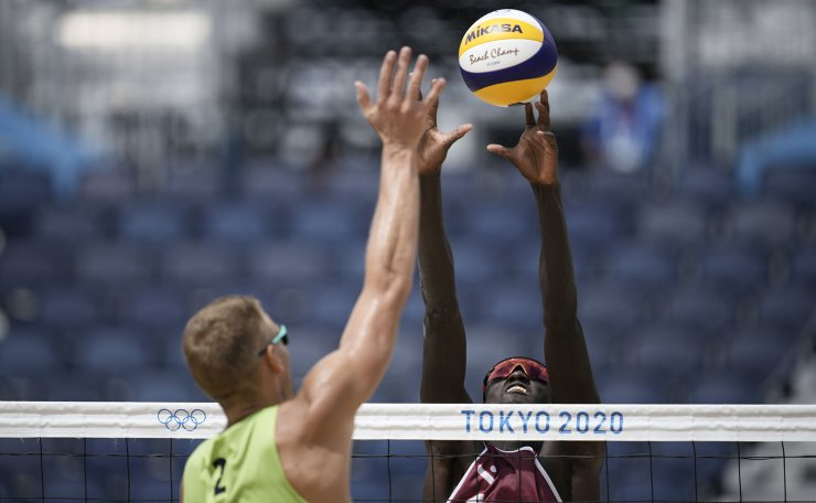 Cherif Younousse, top, of Qatar, takes a shot as Edgars Tocs, of Latvia, defends during a men's beach volleyball Bronze Medal match at the 2020 Summer Olympics, Saturday, Aug. 7, 2021, in Tokyo, Japan. AP