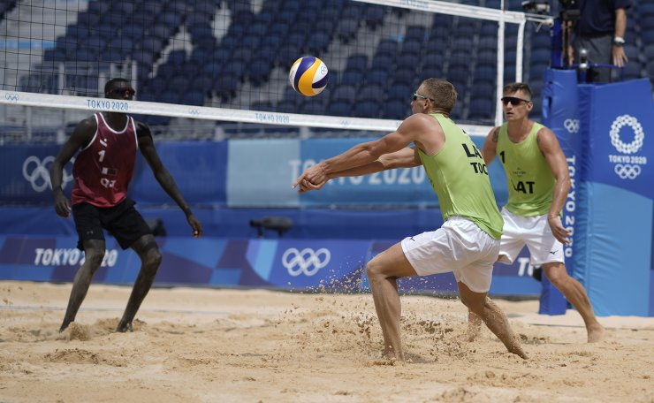 Edgars Tocs, center, of Latvia, takes a shot as teammate Martins Plavins, right, watches while Cherif Younousse, of Qatar, defends during a men's beach volleyball Bronze Medal match at the 2020 Summer Olympics, Saturday, Aug. 7, 2021, in Tokyo, Japan. AP