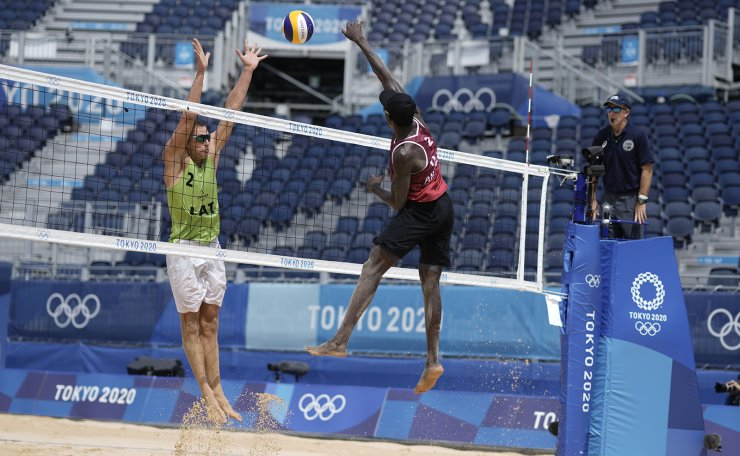 Ahmed Tijan, right, of Qatar takes a shot as Edgars Tocs, of Latvia, defends during a men's beach volleyball Bronze Medal match at the 2020 Summer Olympics, Saturday, Aug. 7, 2021, in Tokyo, Japan. AP