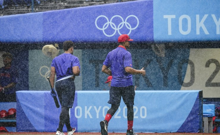 Players from Dominican Republic head to the dugout during a rain storm ahead of the bronze medal baseball game against South Korea at the 2020 Summer Olympics, Saturday, Aug. 7, 2021, in Yokohama, Japan. AP