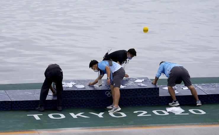 Olympic event volunteers dry off the medal podium after a rain in preparation for the canoe sprint medal ceremonies at the 2020 Summer Olympics, Saturday, Aug. 7, 2021, in Tokyo, Japan. AP