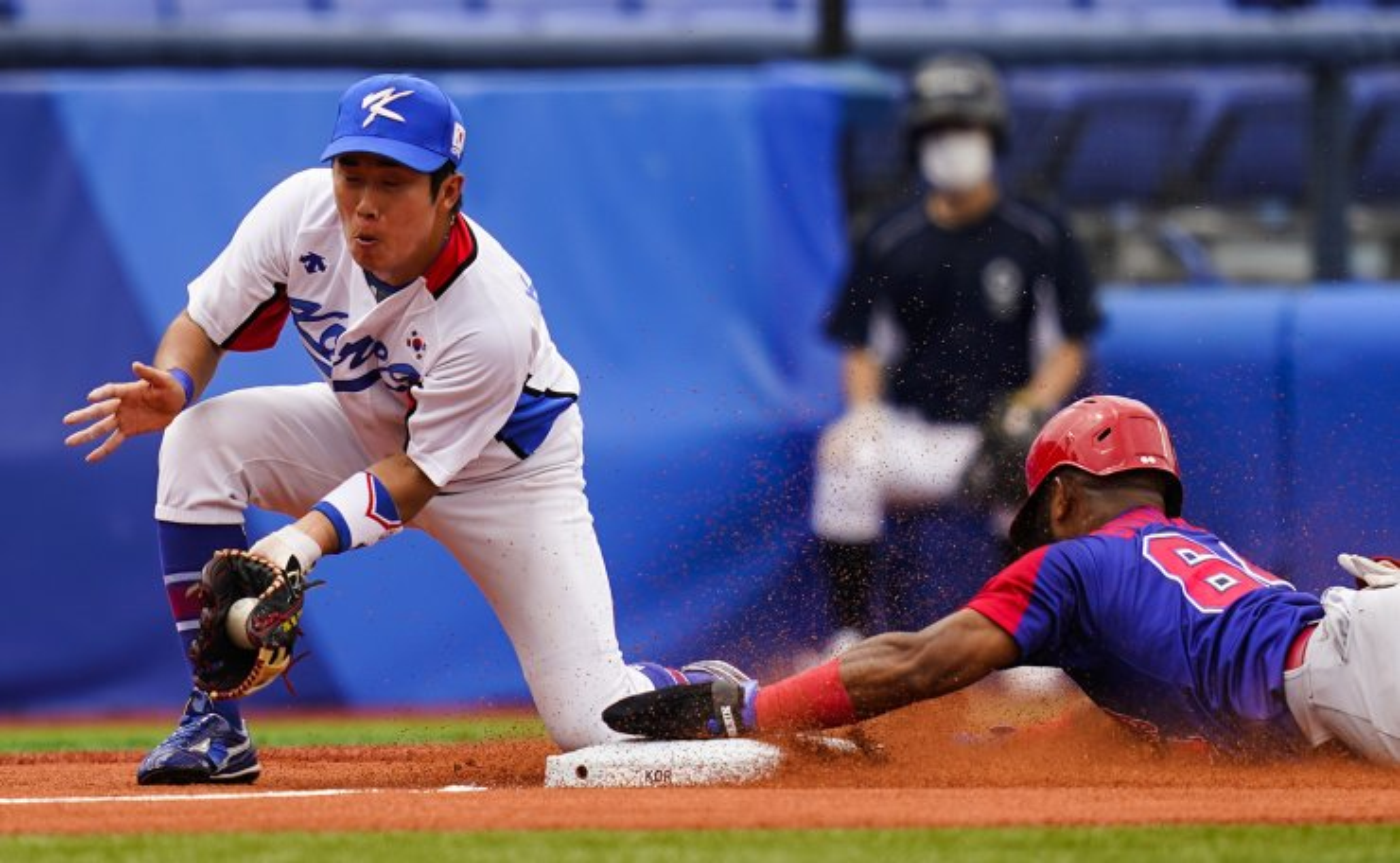 Dominican Republic's Emilio Bonifacio steal third base past Kyoungmin Hur during the bronze medal baseball game at the 2020 Summer Olympics, Saturday, Aug. 7, 2021, in Yokohama, Japan. AP