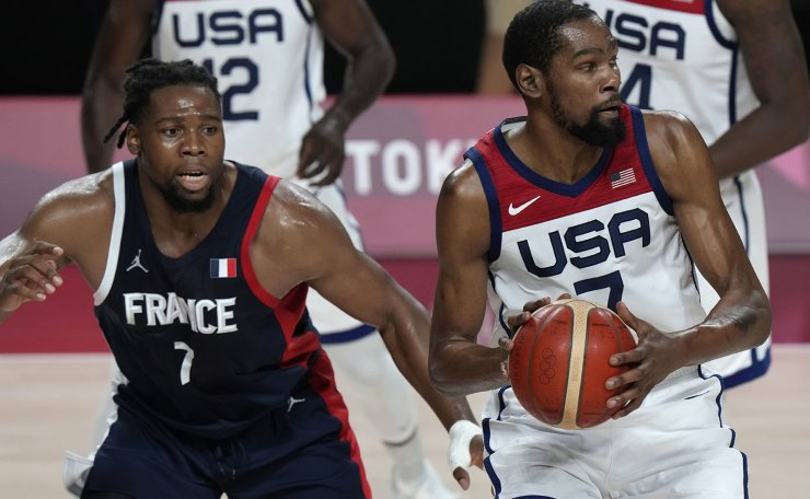 United States' Kevin Durant (7) drives around France's Guerschon Yabusele (7) during men's basketball gold medal game at the 2020 Summer Olympics, Saturday, Aug. 7, 2021, in Saitama, Japan. AP