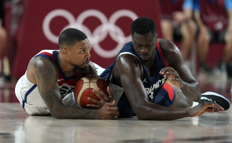 United States' Damian Lillard (6), left, and France's Moustapha Fall (93) fight for a loose ball during men's basketball gold medal game at the 2020 Summer Olympics, Saturday, Aug. 7, 2021, in Saitama, Japan. AP