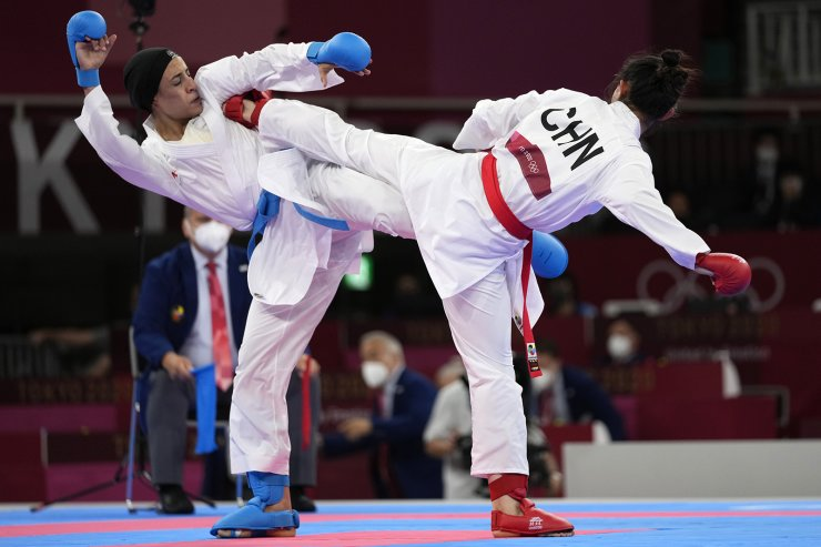 Feryal Abdelaziz of Egypt, left, and Gong Li of China compete in the women's kumite +61kg elimination round for karate at the 2020 Summer Olympics, Saturday, Aug. 7, 2021, in Tokyo, Japan. AP