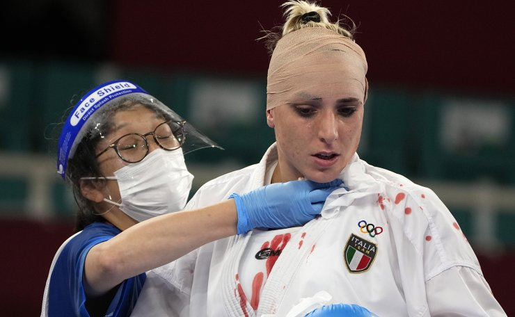 A staff member bandages Silvia Semeraro of Italy after she was injured while competing against Meltem Hocaoglu Akyol of Turkey in the women's kumite +61kg elimination round for karate at the 2020 Summer Olympics, Saturday, Aug. 7, 2021, in Tokyo, Japan. AP