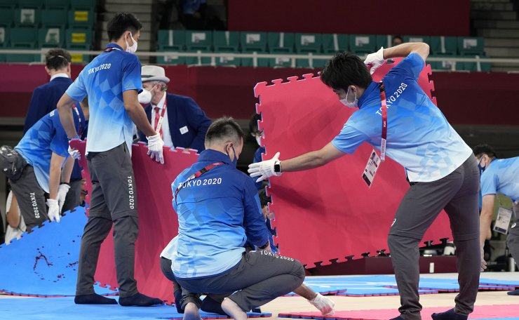Staff members remove sections of the mat after an injury during the bout between Silvia Semeraro of Italy and Meltem Hocaoglu Akyol of Turkey in the women's kumite +61kg elimination round for karate at the 2020 Summer Olympics, Saturday, Aug. 7, 2021, in Tokyo, Japan. AP