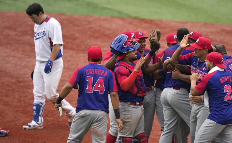 South Korea's Hyunsoo Kim, left, leaves the field as the Dominican Republic players celebrate the team's 10-6 win in the bronze medal baseball game at the 2020 Summer Olympics, Saturday, Aug. 7, 2021, in Yokohama, Japan. AP
