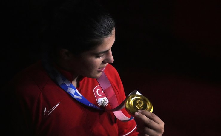 Gold medalist Turkey's Busenaz Surmeneli looks at her medal after the ceremony for their women's welter weight 64-69kg competition at the 2020 Summer Olympics, Saturday, Aug. 7, 2021, in Tokyo, Japan. AP