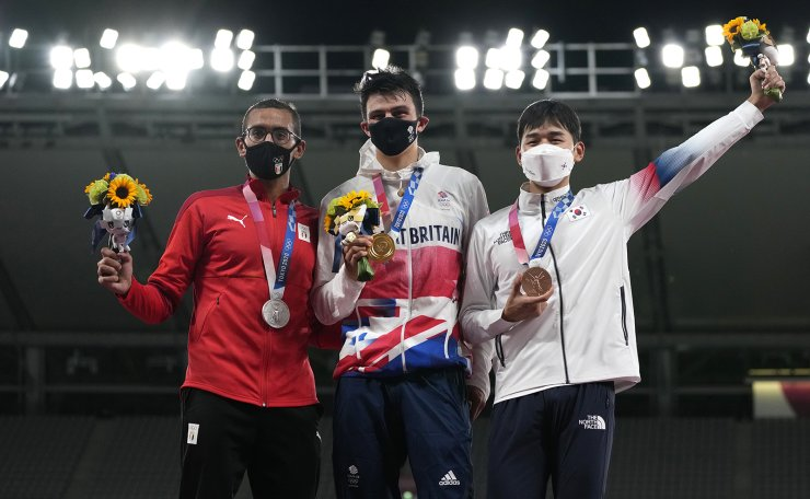 Silver medalist, Ahmed Elgendy of Egypt, left, gold medalist Joseph Choong of Britain, center, and Bronze medalist Jun Woongtae of South Korea celebrate on the podium during the medal ceremony for the men's modern pentathlon at the 2020 Summer Olympics, Saturday, Aug. 7, 2021, in Tokyo, Japan. AP