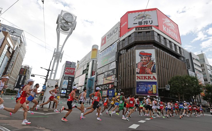 Runners move past the Susukino district while competing in the men's marathon final during the Tokyo 2020 Olympic Games in Sapporo on August 8, 2021. AFP