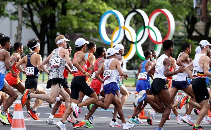 Runners move past the Olympic symbol while competing in the men's marathon final during the Tokyo 2020 Olympic Games in Sapporo on August 8, 2021. AFP