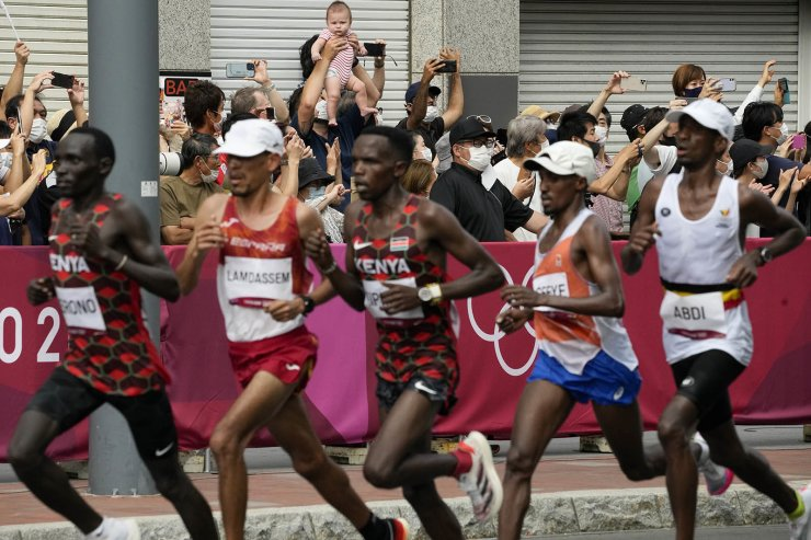 Fans watches as runners compete during the men's marathon at the 2020 Summer Olympics, Sunday, Aug. 8, 2021, in Sapporo, Japan. AP