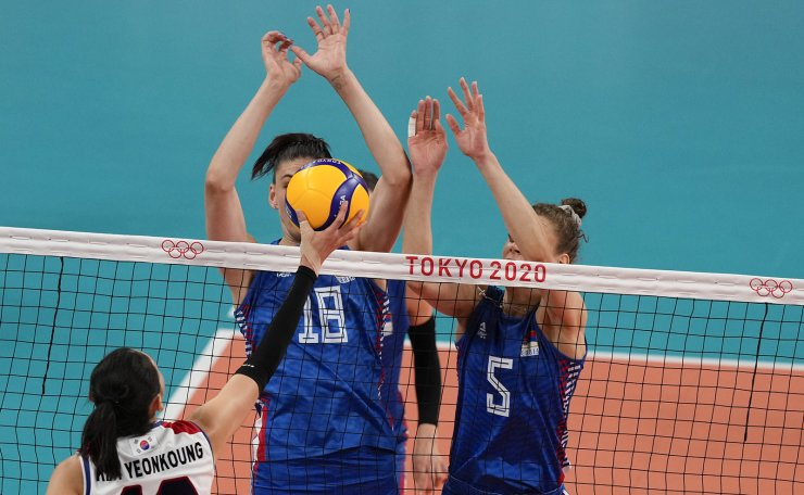 Korea's Kim Yeon Koung, right, shoots as Serbia's Tijana Boskovic, center, and Mina Popovic block during the bronze medal match in women's volleyball at the 2020 Summer Olympics, Sunday, Aug. 8, 2021, in Tokyo, Japan. AP